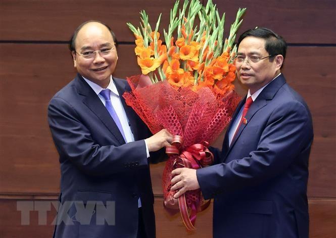 Thủ tướng Phạm Minh Chính tặng hoa Chủ tịch nước Nguyễn Xuân Phúc, Thủ tướng Chính phủ nhiệm kỳ 2016-2021. (Nguồn: TTXVN)