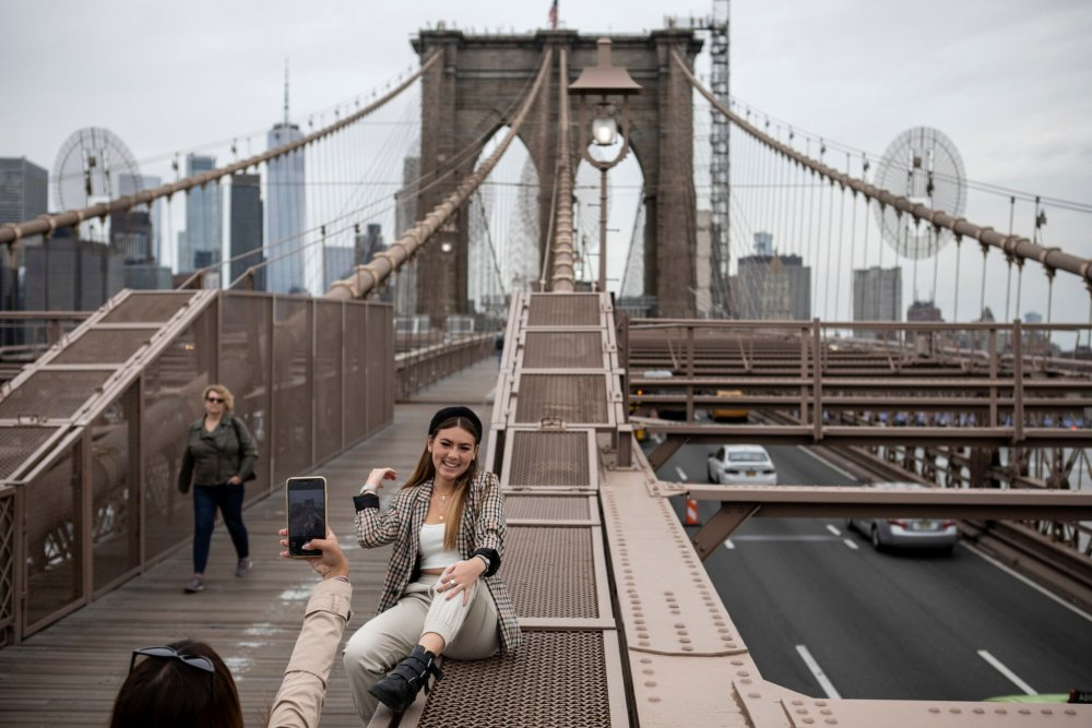 A visitor from Mexico took photos on the Brooklyn Bridge. The number of tourists to New York City plunged to 22 million last year from 66 million in 2019.Credit...Kirsten Luce for The New York Times