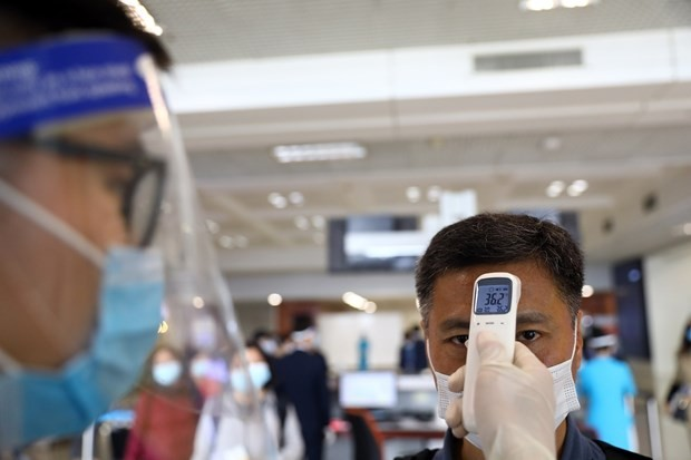 A man gets temperature check before getting on a flight at Noi Bai International Airport in Hanoi (Photo: VNA)